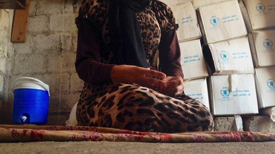 FILE - In this file photo taken Wednesday, Oct. 8, 2014, a 15-year-old Yazidi girl captured by ISIS and forcibly married to a militant in Syria sits on the floor of a one-room house she now shares with her family after escaping in early August, while speaking in an interview with The Associated Press in Maqluba, a hamlet near the Kurdish city of Dahuk, 260 miles northwest of Baghdad.  (AP Photo/Dalton Bennett, File)