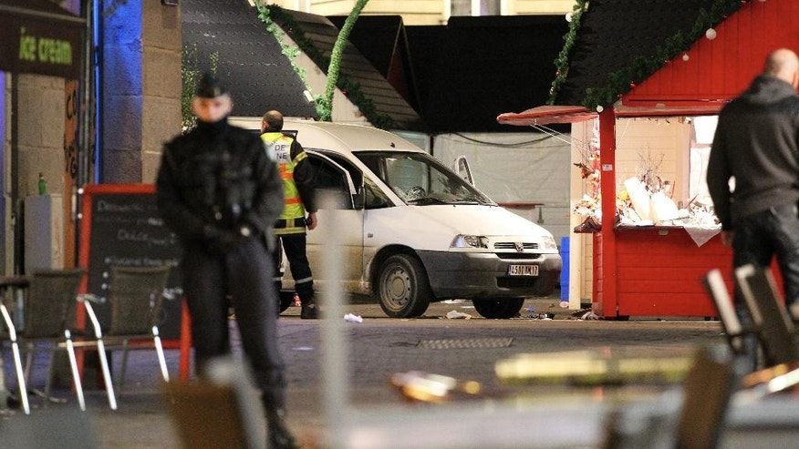 Police officers guard the van that crashed into a French Christmas market in Nantes, western France, Monday, Dec. 22, 2014. France's top security official says the driver stabbed himself several times after the incident. Eleven people including the driver were injured in the accident, which happened at a busy market full of holiday shoppers. (AP Photo/Laetitia Notarianni)