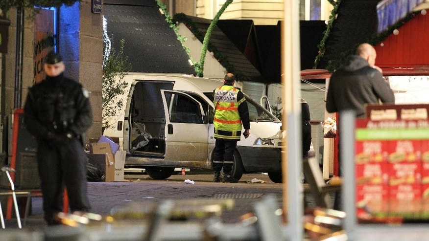 A police officer guards the van that crashed into a French Christmas market in Nantes, western France, Monday, Dec. 22, 2014. French authorities urged calm after a series of attacks across the country left dozens of people injured, and said there was no evidence the attacks were connected by any terrorist motive. In the latest incident, 11 people were injured after a driver crashed his van into a crowded Christmas market in western France Monday evening. The driver then stabbed himself several times and is among five people hospitalized in serious condition, authorities said. (AP Photo/Laetitia Notarianni)