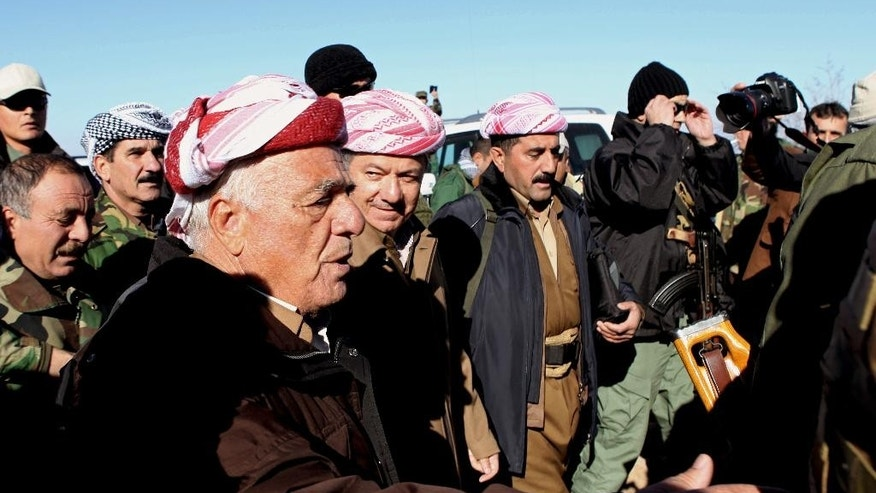 FILE - In this Sunday, Dec. 21, 2014 file photo, Kurdistan Iraqi regional government President Massoud Barzani, center, arrives to support Kurdish forces as they head to battle Islamic State militants, on the summit of Mount Sinjar, in the town of Sinjar, Iraq. On Sunday, Barazani, visited the command center on the mountain top, vowing to his fighters that they would crush the Islamic State fighters wherever they find them. (AP Photo/Zana Ahmed, File)