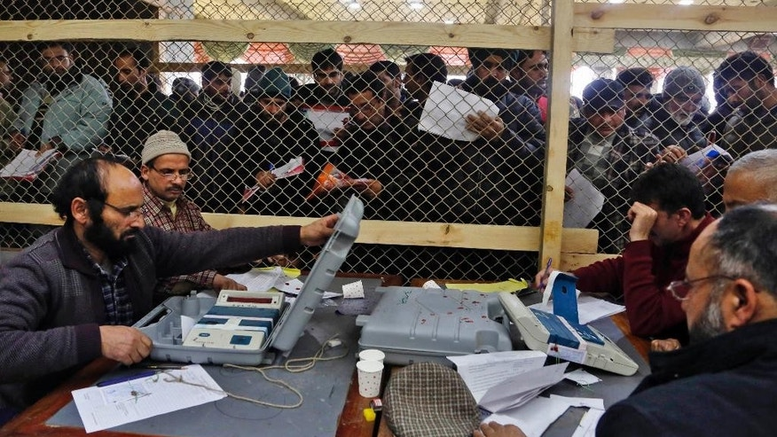Kashmiri polling officials count the votes on an electronic voting machine check inside the counting centre in Srinagar, India, Tuesday, Dec. 23, 2014. Counting for all the 87 assembly seats in Jammu and Kashmir state began Tuesday. (AP Photo/Mukhtar Khan)