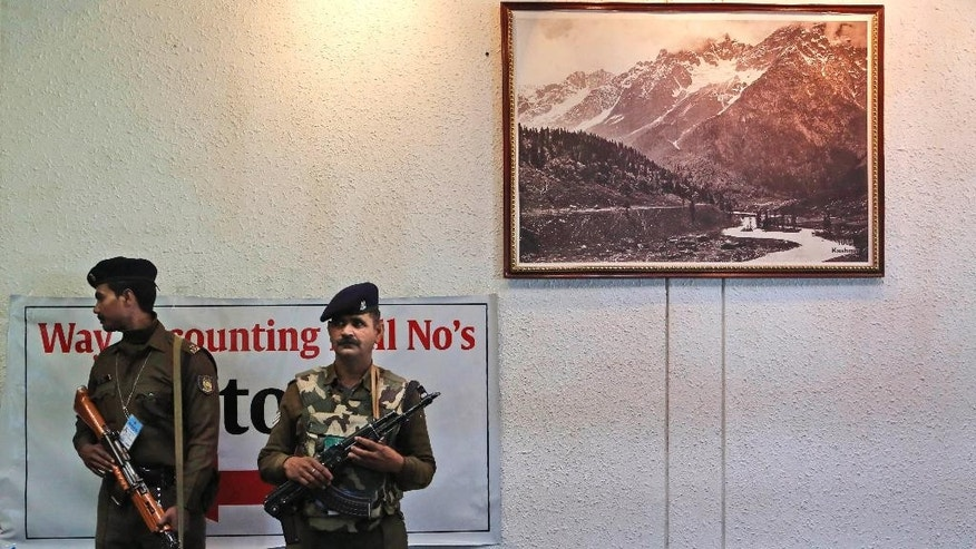 Indian paramilitary soldiers stand guard inside a counting centre in Srinagar, India, Tuesday, Dec. 23, 2014. Counting for all the 87 assembly seats in Jammu and Kashmir state began Tuesday. (AP Photo/Mukhtar Khan)