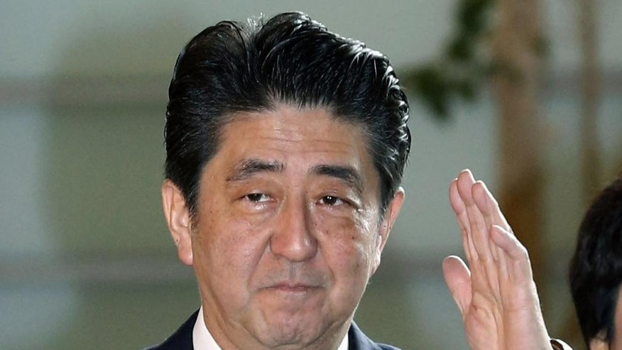 Japan's Prime Minister Shinzo Abe arrives at his official residence in Tokyo Wednesday, Dec. 24, 2014. Japan was preparing Wednesday to name Abe to his next term in office following his party's victory in a Dec. 14 snap election. Abe's Cabinet disbanded early in the day as a ritual first step. The parliament was to convene in the afternoon to elect Abe as prime minister. Abe is due to then appoint a new cabinet. (AP Photo/Kyodo News) JAPAN OUT, MANDATORY CREDIT