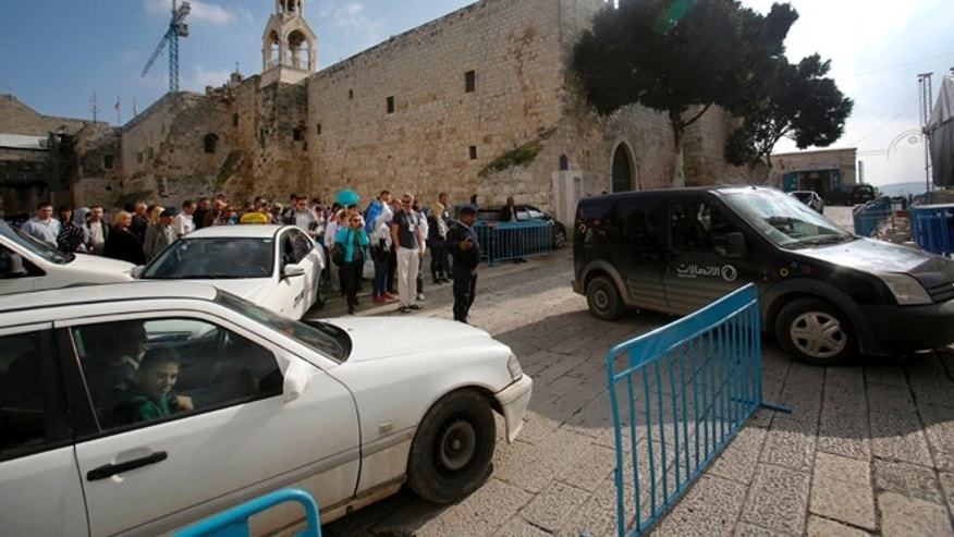 Dec. 14, 2014: Tourists walk and cars drive past the Church of the Nativity in Bethlehem, West Bank. Its Christmas season and the little town of Bethlehem is jammed with a big-city problem: Traffic snarling streets everywhere, including around the church marking the spot where tradition says Jesus was born.