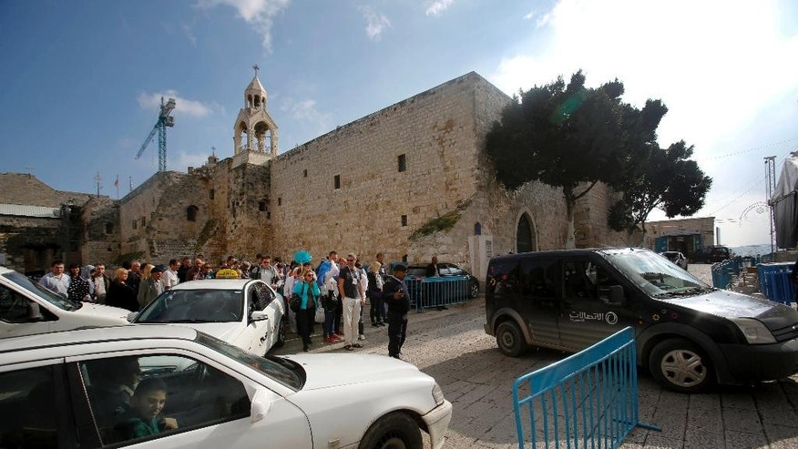 In this  Sunday, Dec. 14, 2014, photo tourists walks and cars drive past the Church of the Nativity in Bethlehem, West Bank. It's Christmas season and the little town of Bethlehem is jammed with a big-city problem: Traffic snarling streets everywhere, including around the church marking the spot where tradition says Jesus was born. The city is considering a dramatic solution to the problem _ digging a tunnel under Manger Square. (AP Photo/Nasser Shiyoukhi)
