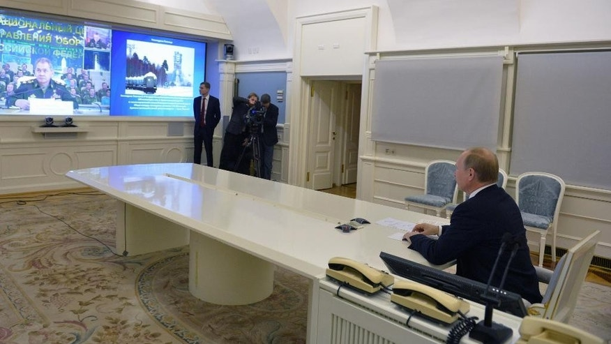 Russian President Vladimir Putin speaks with Defense Minister Sergei Shoigu, as he watches a launch of Angara-A5 rocket booster at Plesetsk Cosmodrome by live video link in Moscow, Russia, Tuesday, Dec. 23, 2014. (AP Photo/RIA Novosti, Alexei Druzhinin, Presidential Press Service)