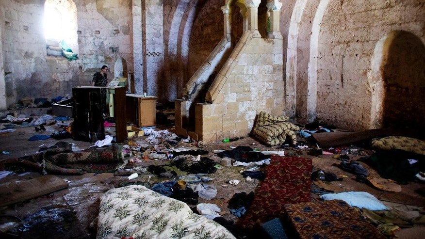 FILE - This file photo made on Thursday, May 1, 2014, shows belongings of Syrian rebels inside a chapel at Crac des Chevaliers, the world's best preserved medieval Crusader castle, in Syria.  A U.N. agency says Tuesday, Dec. 23, 2014 that  satellite imagery shows that at least 290 cultural heritage sites in Syria have been damaged by the country's civil war. (AP Photo/Dusan Vranic, File)