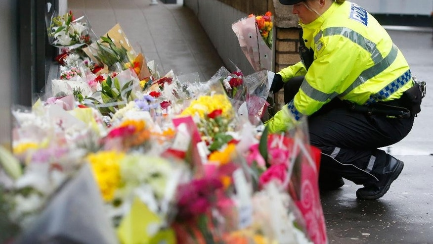 A police officer looks at flowers on Tuesday Dec. 23, 2014,  left close to the scene in George Square, Glasgow Scotland where on Monday a garbage truck crashed into a group of pedestrians which has left a number of people dead. (AP Photo/Danny Lawson/PA)  UNITED KINGDOM OUT
