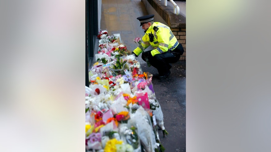 A police officer places flowers on Tuesday Dec. 23, 2014, close to the scene in George Square, Glasgow Scotland where on Monday a garbage truck crashed into a group of pedestrians which has left a number of people dead. (AP Photo/Danny Lawson/PA)  UNITED KINGDOM OUT