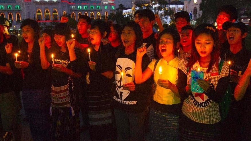 Activists holding candles offer prayers for a victim who was killed during a crackdown on protesters at a copper mine in northwestern Myanmar, Tuesday, Dec. 23, 2014, at a park in front of the city hall in Yangon, Myanmar. Villagers protesting their eviction for expansion of the Chinese-backed copper mine are continuing a stand-off with security forces, a day after their confrontation left one woman dead and 20 other people hurt. (AP Photo/Khin Maung Win)