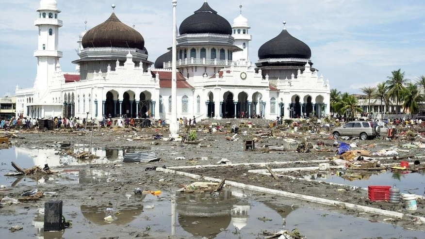 FILE - In this Dec. 27, 2004 file photo, debris left by southern Asia's massive earthquake and tidal waves are seen around the Baiturrahman Grand Mosque in Banda Aceh, about 240 kilometers (150 miles) from the earthquake's epicenter, Indonesia. When the powerful tsunami smashed into this Indonesian city ten years ago, the only structures left standing in many neighborhoods were mosques. For the hundreds who found refuge within their walls, the buildings' lifesaving role has not been forgotten - and for many, that experience strengthened their faith. Architectural experts say the mosques in Banda Aceh survived because they were sturdily built and had stronger foundations than surrounding structures, many of which were likely constructed of shoddier materials. But many survivors believe the mosques were spared by divine intervention. (AP Photo/Achmad Ibrahim, File)