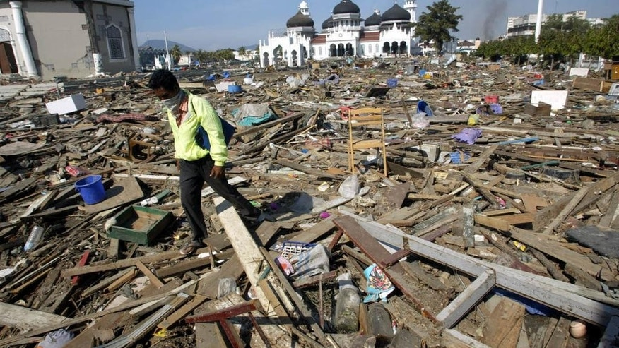 FILE - In this Dec. 29, 2004 file photo, an Acehnese man walks through debris near the Baiturrahman Grand Mosque in Banda Aceh, about 240 kilometers (150 miles) from the earthquake's epicenter, Indonesia. When the powerful tsunami smashed into this Indonesian city ten years ago, the only structures left standing in many neighborhoods were mosques. For the hundreds who found refuge within their walls, the buildings' lifesaving role has not been forgotten - and for many, that experience strengthened their faith. Architectural experts say the mosques in Banda Aceh survived because they were sturdily built and had stronger foundations than surrounding structures, many of which were likely constructed of shoddier materials. But many survivors believe the mosques were spared by divine intervention. (AP Photo/Dita Alangkara, File)