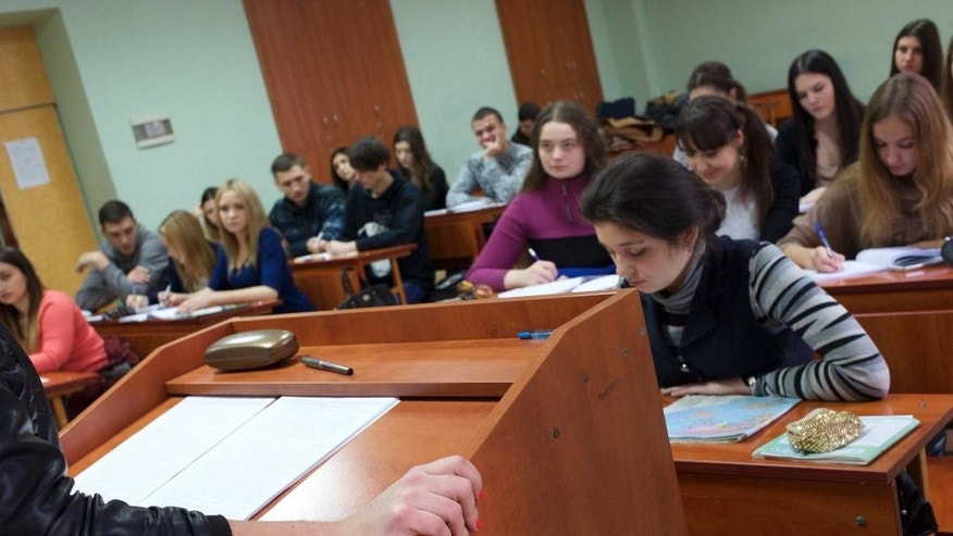 In this Wednesday, Dec. 10, 2014 photo, students attend a lecture at the Donetsk National University in Donetsk, eastern Ukraine. In eastern Ukraine, where the country's pro-Russian insurgency has claimed thousands of lives, the region's top university is a major victim of the bitterness and rifts the fighting has caused. (AP Photo/Balint Szlanko)