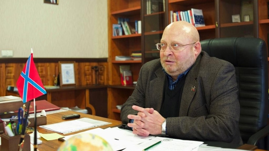 In this Wednesday, Dec. 10, 2014 photo, Sergei Baryshnikov, the new pro-Russian head of Donetsk National University, speaks in his office at the university in Donetsk, eastern Ukraine. Baryshnikov, who stayed behind in Donetsk to head up the rebel-controlled university, said work is now afoot to modify the curriculum in line with the evolving situation. Many teachers and students have fled the rebel-controlled regions in eastern Ukraine to continue their studies in territories under government control. A flag on the table is the self-proclaimed Novorossiya. There is a portrait of Russian President Vladimir Putin on the wall in the background. (AP Photo/Balint Szlanko)