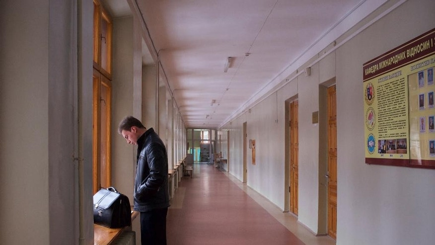 In this Wednesday, Dec. 10, 2014 photo, a man stands in a corridor at the Donetsk National University in Donetsk, eastern Ukraine. In eastern Ukraine, where the country's pro-Russian insurgency has claimed thousands of lives, the region's top university is a major victim of the bitterness and rifts the fighting has caused. (AP Photo/Balint Szlanko)