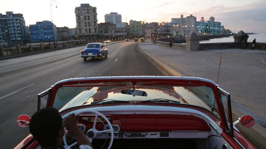 Michel Salgado drives his 1957 Mercury Monterrey convertible car along the Malecon in Havana, Cuba, Sunday Dec. 21, 2014.  U.S. car sales have been banned in Cuba since 1959. Cubans have been have been forced to patch together Fords, Chevrolets and Chryslers that date back to before Fidel Castro's revolution, which can make it appear like the country is stuck in a 1950s time warp. Since the Communist economic system isn't likely to change soon, many of those cars will have to stay on the road for years. (AP Photo/Desmond Boylan)