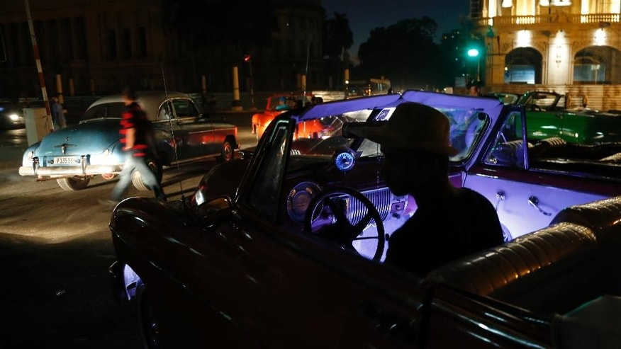 A driver waits for customers to take a spin around the city in classic American convertible car in Havana, Cuba. Sunday Dec. 21, 2014. U.S. car sales have been banned in Cuba since 1959. Cubans have been have been forced to patch together Fords, Chevrolets and Chryslers that date back to before Fidel Castro's revolution which can make it appear like the country is stuck in a 1950s time warp. Since the Communist economic system isn't likely to change soon, many of those cars will have to stay on the road for years. (AP Photo/Desmond Boylan)