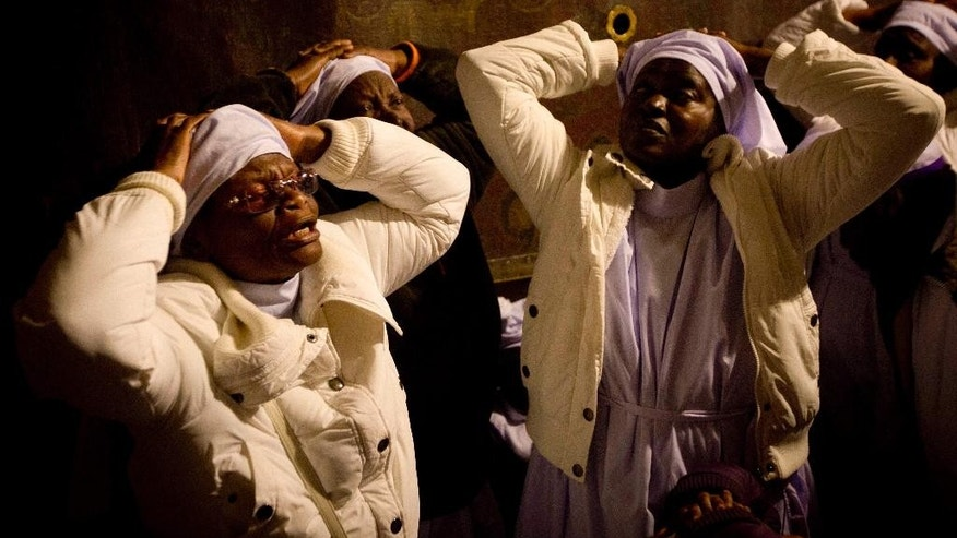 Christian pilgrims from Nigeria pray inside the Grotto of the Church of the Nativity, traditionally believed by Christians to be the birthplace of Jesus Christ, in the West Bank city of Bethlehem on Christmas Eve Wednesday, Dec. 24, 2014. (AP Photo/Majdi Mohammed)