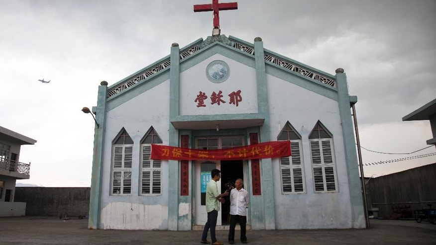 "In this photo taken July 15, 2014, Pastor Tao Chongyin, left, speaks with church member Fan Liang'an in front of the Wuxi Christian Church with the words ""Church of Jesus"" in red, in Longwan, Wenzhou in eastern China's Zhejiang province. When one rural village re-erected a cross in the summer, authorities put it under a 24-hour watch, which has now gone on for nearly five months. ""This year's Christmas has been exceptional, as a group of uniformed men have been helping us move tables, direct traffic, and guard holiday decorations as well as the front door, the back door, the warehouse and the sanctuary,"" Tao wrote on a social media site. (AP Photo/Didi Tang)"