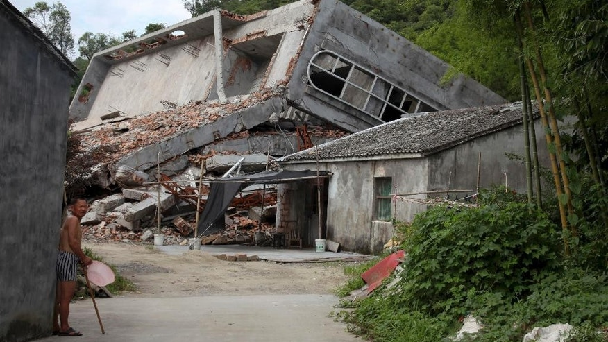 In this photo taken July 16, 2014, a man stands near the razed remains of a Catholic church in a village in Pingyang county of Wenzhou in eastern China's Zhejiang province.  Like many Christians in the eastern Chinese province of Zhejiang, will worship this Christmas under a cross-less roof. Provincial authorities have toppled crosses from more than 400 churches, and even razed some worship halls in a province-wide crackdown on building code violations. (AP Photo/Didi Tang)