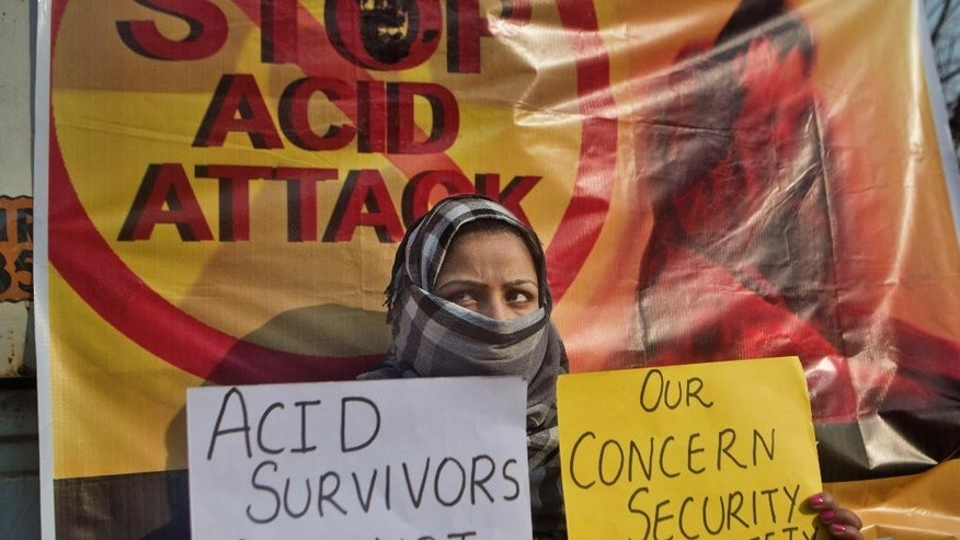 FILE - In this Dec. 12, 2014 file photo, Kashmiri law student Fareen holds placards as she participates in a protest against an acid attack on a woman in Srinagar, Indian controlled Kashmir, a day after a young law student was attacked with acid that left her in a critical condition. Two men riding a motorcycle threw acid on a woman in a crowded neighborhood in New Delhi, causing serious injuries, police said Wednesday, Dec. 24. The attack was captured on closed-circuit TV and was being investigated, police officer Suresh Chand said. It took place Tuesdaym, Dec. 23 when the two masked men rode past the woman in a crowded shopping area and brazenly flung acid at her face. (AP Photo/Dar Yasin, File)