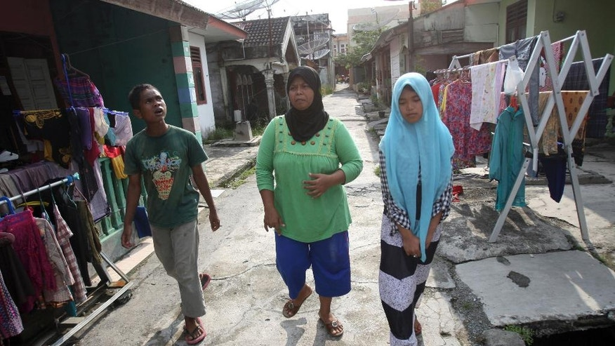 In this Tuesday, Oct. 21, 2014 photo, tsunami survivor Jamaliah, center, walks with Raudhatul Jannah, right, and Arif Pratama, whom she believes to be her two children separated with her when the village they lived in was hit by the killer waves in 2004, in their neighborhood in Meulaboh, Aceh province, Indonesia. Although there has been no DNA test the parents are convinced that the children belong them. (AP Photo/Binsar Bakkara)