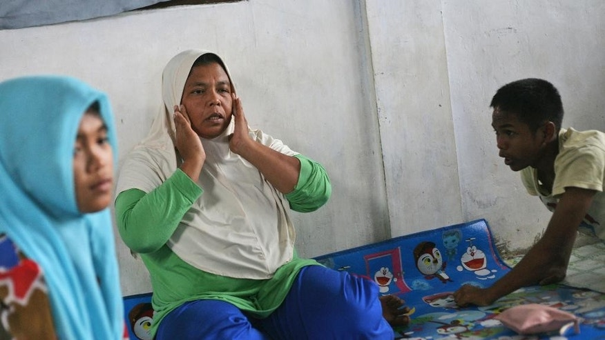 In this Tuesday, Oct. 21, 2014 photo, tsunami survivor Jamaliah, center, sits in her living room with Raudhatul Jannah, left, and Arif Pratama, whom she believes to be her two children separated with her when the village they lived in was hit by the killer waves in 2004, in their house in Meulaboh, Aceh province, Indonesia. Although there has been no DNA test the parents are convinced that the children belong them. (AP Photo/Binsar Bakkara)