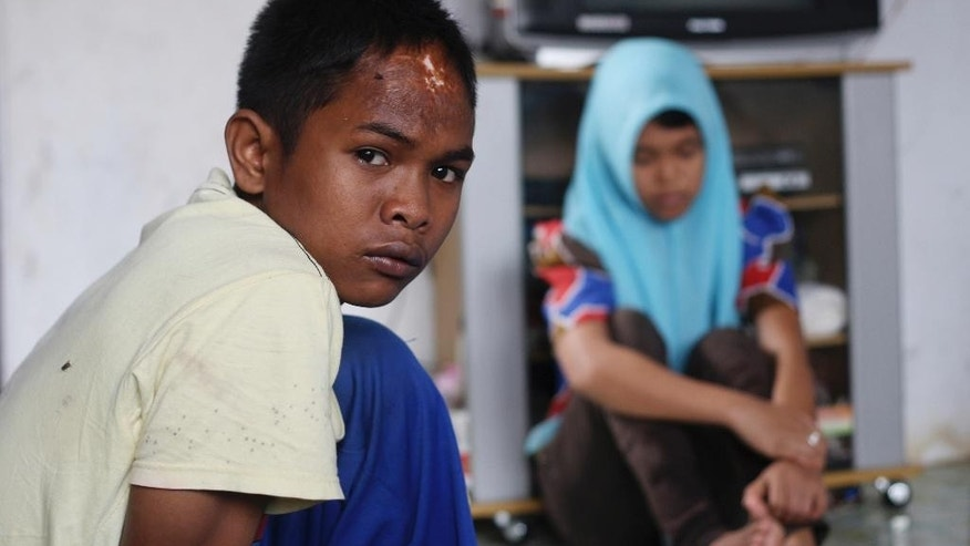 In this Tuesday, Oct. 21, 2014 photo, Arif Pratama, left, and Raudhatul Jannah who are believed to be the two children of tsunami survivor Jamaliah after being separated with her when the village they lived in was hit by the killer waves in 2004, sit on the living room of their house during an interview in Meulaboh, Aceh province, Indonesia. Although there has been no DNA test the parents are convinced that the children belong them. (AP Photo/Binsar Bakkara)