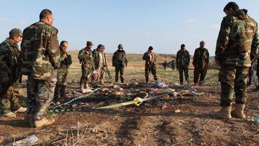 Dec. 22, 2014: Kurdish Peshmerga forces inspect a site in Hardan village in northern Iraq, where Islamic State group fighters allegedly executed people from the Yazidi sect captured when they swept through the area in August. The Yazidis want to learn the fate of hundreds of missing relatives and neighbors and they fear they know where they are: Four mounds of freshly dug dirt in nearby fields they believe are graves.