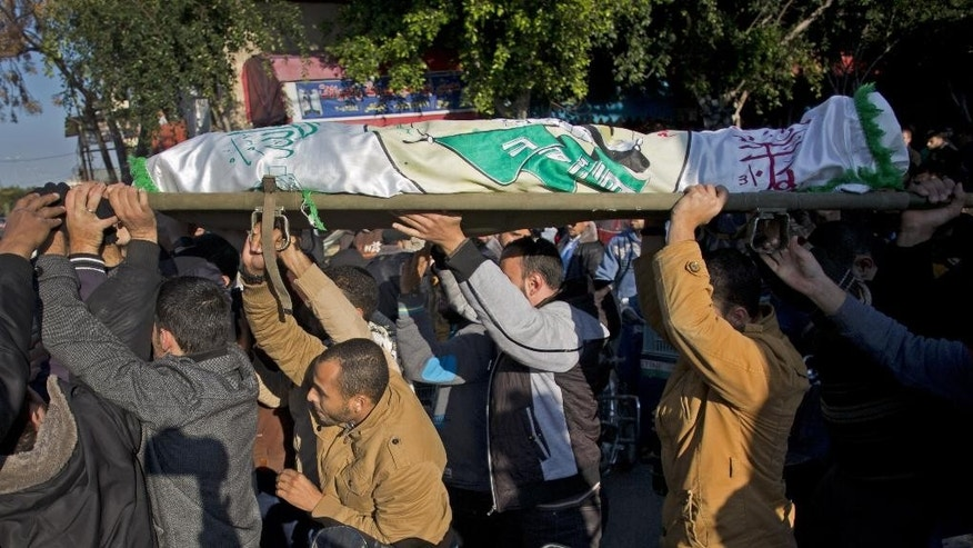 Palestinian mourners carry the body of Hamas militant, Tayseir Smeiry, who was killed by an Israeli tank fire near the border fence between Gaza Strip and Israel, during his funeral in Town of Khan Younis, southern Gaza Strip, Wednesday, Dec. 24, 2014. Israel deployed tank fire and an airstrike on targets in Gaza after its troops came under attack by Palestinian snipers as they were on patrol on the Israeli side of the border, the military said Wednesday. (AP Photo/Khalil Hamra)