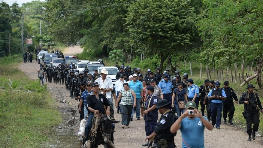 Riot police enter the town of El Tule, Nicaragua after  they cleared a roadblock erected by residents, Wednesday Dec. 24, 2014. National police special forces and soldiers fired tear gas and rubber bullets at demonstrators who had blocked the Pan American highway to protest against a proposed transoceanic canal. Thousands had maintained the roadblock since workers broke ground Monday for the $50 billion canal, which will require the expropriation of land. (AP Photo/Oscar Navarrete)
