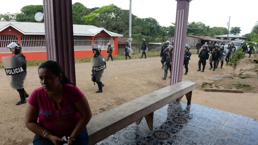 A woman sits as riot police enter the town of El Tule, Nicaragua after  they cleared a roadblock erected by residents, Wednesday Dec. 24, 2014. National police special forces and soldiers fired tear gas and rubber bullets at demonstrators who had blocked the Pan American highway to protest against a proposed transoceanic canal. Thousands had maintained the roadblock since workers broke ground Monday for the $50 billion canal, which will require the expropriation of land. (AP Photo/Oscar Navarrete)