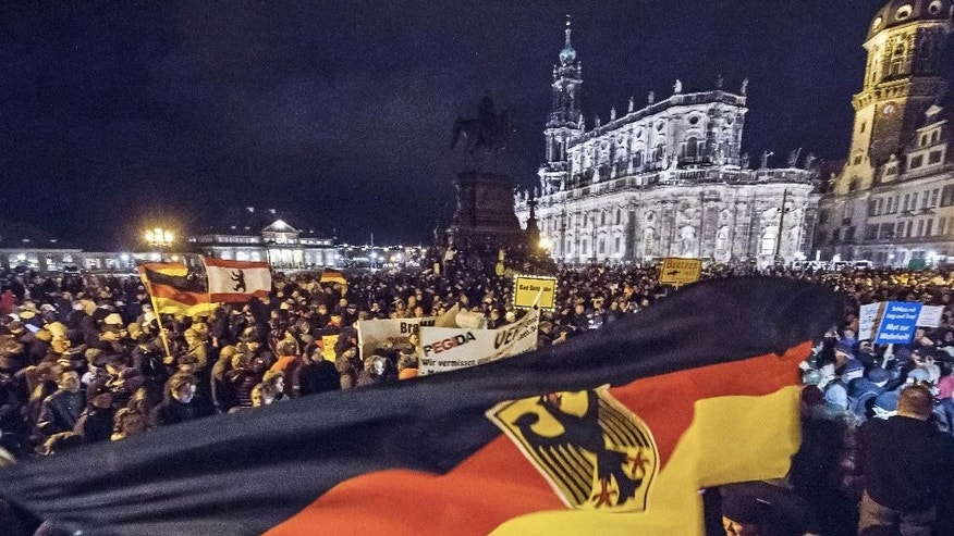 Participants of a rally called 'Patriotic Europeans against the Islamization of the West' (PEGIDA) hold German flags and lights during a demonstration entitled 'Christmas With Pegida' between the bronze equestrian statue of King John of Saxony, left, and the Dresden Cathedral, or the Cathedral of the Holy Trinity, in Dresden, eastern Germany, Monday, Dec. 22, 2014. For the past ten weeks, activists protesting Germany's immigration policy and the spread of Islam in the West have been marching each Monday. (AP Photo/Jens Meyer)