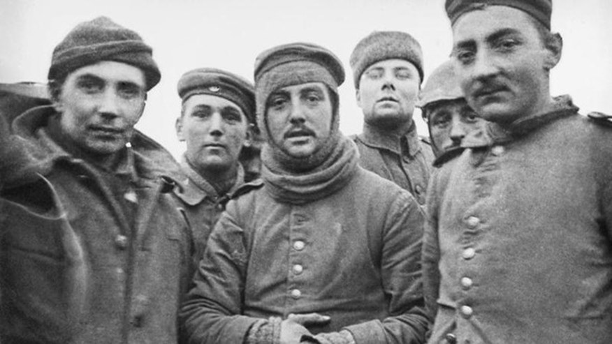 In this image provided by the Imperial War Museum, World War I German and British soldiers stand together on the battlefield near Ploegsteert, Belgium in Dec. 1914. Soldiers who had been killing each other for months climbed out of their soggy trenches to seek a shred of humanity amid the horrors of World War I.