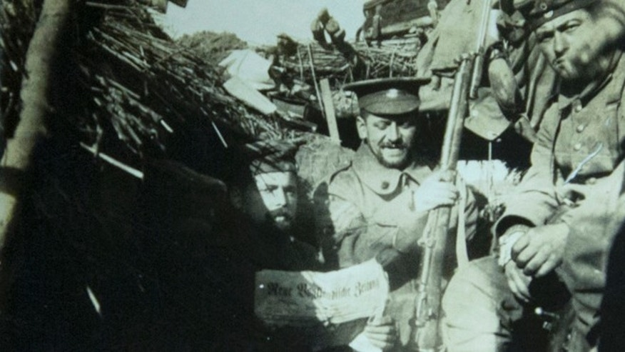 In this photo taken from an image in the collection at In Flanders Fields Museum provided by the family of German soldier Kurt Zehmisch, a German World War I soldier of the 103rd Saxon Regiment wears the hat of a British soldier as he sits in a trench with other German soldiers in Warneton, Belgium.