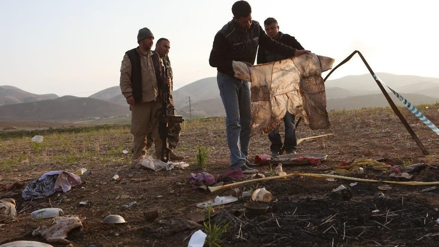 In this Monday, Dec. 22, 2014 photo, Khaled Wase, a 28-year-old Yazidi man who escaped from his village on Aug. 4th as Islamic State militants took over the area, picks up a piece of clothing as he returns to see if he can find the bodies of missing neighbors and relatives in Hardan village in northern Iraq. A handful of Yazidis who fled this tiny northern Iraqi hamlet in August have returned after Kurdish fighters drove out the extremists in recent days. They want to learn the fate of hundreds of missing relatives and neighbors and they fear they know where they are: Four mounds of freshly dug dirt in nearby fields they believe are graves. (AP Photo/Dalton Bennett)