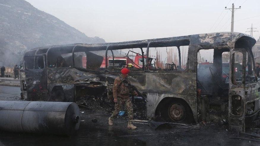FILE - In this file photo taken Saturday, Dec. 13, 2014, an Afghan soldier inspects a damaged bus at the site of a suicide attack by the Taliban in Kabul, Afghanistan. With U.S.-led forces shifting to a supporting role at the end of this month, Afghanistan will have to chart its own course after the country's bloodiest year since the 2001 invasion, a year which saw record casualties among Afghan civilians and security forces alike. (AP Photo/Rahmat Gul, File)