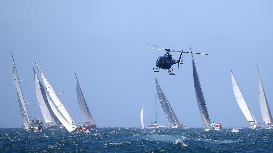 A helicopter hovers low to get images of some of the competitors during the start of the Sydney Hobart yacht race in Sydney, Friday, Dec. 26, 2014. The 117-boat fleet is expected to have a bumpy first night at sea, with southerly gusting up to 30 knots and choppy conditions. (AP Photo/Rick Rycroft)