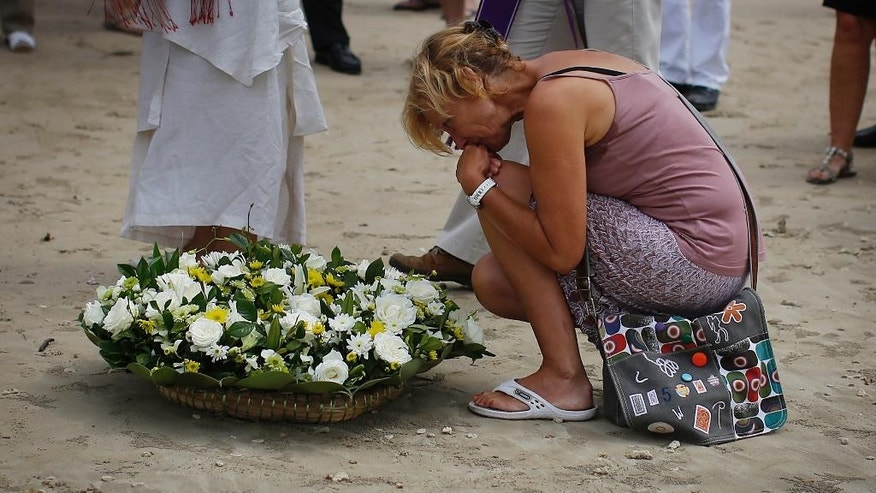 A relative of the Asian tsunami holds back her tears as she lays a white rose on the beach during a commemoration and religious ceremony for German, Austrian and Swiss victims of the Asian tsunami, in Khao Lak, Thailand, Friday, Dec. 26, 2014. December 26 marks the 10th anniversary of one of the deadliest natural disasters in world history: a tsunami, triggered by a massive earthquake off the Indonesian coast, that left more than 230,000 people dead in 14 countries and caused about $10 billion in damage. (AP Photo/Wong Maye-E)