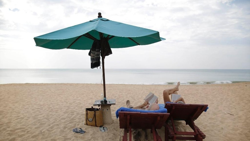 Tourists enjoy a quiet afternoon reading on the beach Thursday, Dec. 25, 2014 in Khao Lak, Thailand, which was not spared from massive destruction from the Asian tsunami 10 years ago. Dec. 26 marks the 10th anniversary of one of the deadliest natural disasters in world history: a tsunami, triggered by a massive earthquake off the Indonesian coast, that left more than 230,000 people dead in 14 countries and caused about $10 billion in damage  (AP Photo/Wong Maye-E)