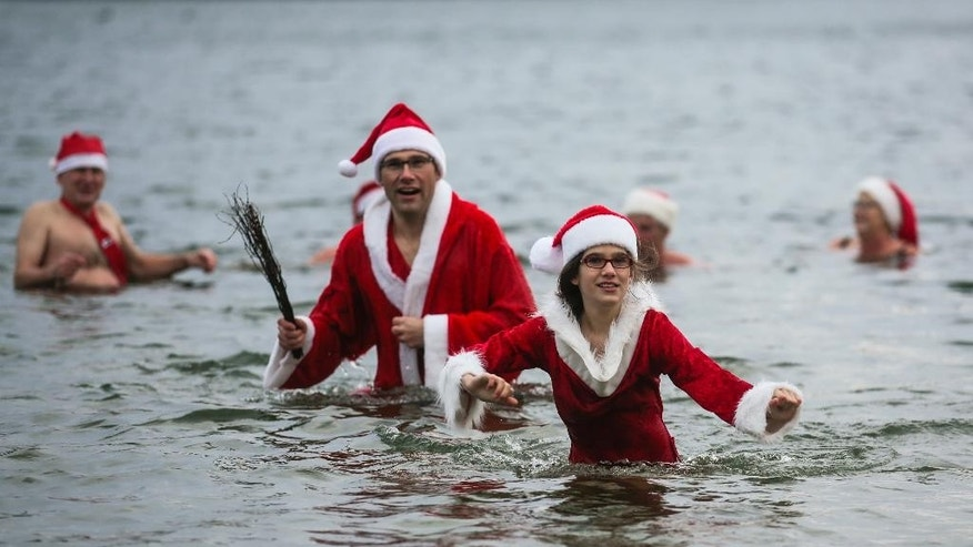 Dec. 25, 2014: Amelie and her father Mario leaves the Oranke Lake during the annual Christmas Swimming of the winter and ice swimming club 'Seehunde Berlin', (Berlin Seals), in Berlin. (AP)
