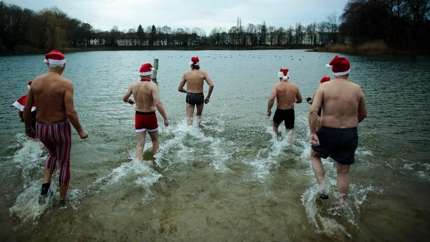 Dec. 25, 2014: Members of the winter and ice swimming club 'Seehunde Berlin' (Berlin Seals), wearing Christmas themed hats, enter the chilly Oranke Lake during the annual Christmas swim in Berlin. (AP)