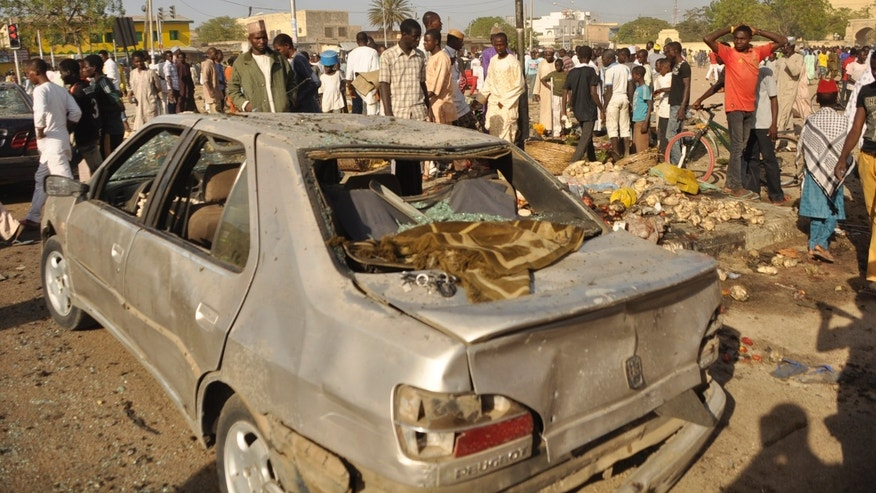 Nov. 28, 2014: People gather at the site of a bomb explosion in Kano, Nigeria