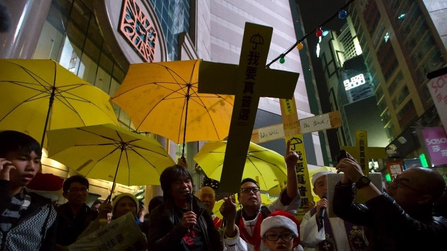 Pro-democracy protesters hold yellow umbrellas and paper crosses during in the early hours of Christmas Day in the Causeway Bay shopping district in Hong Kong Thursday, Dec. 25, 2014 as they demand genuine universal suffrage.  (AP Photo/Kin Cheung)