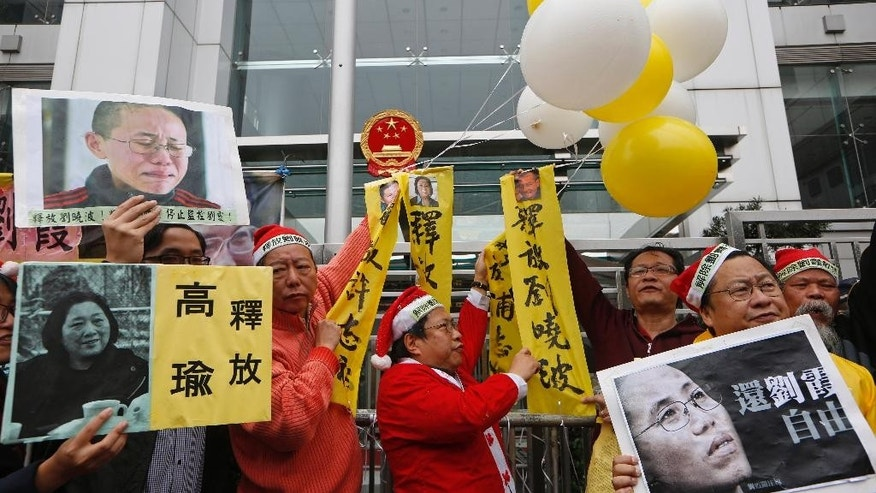 Anti-Beijing protesters dressed in Santa Claus costumes, hold balloons and placards with portrait of Liu Xia, top left, and right, the detained wife of Chinese Nobel Peace laureate Liu Xiaobo and jailed journalist Gao Yu, bottom left, during a rally outside the Chinese liaison office in Hong Kong Thursday, Dec. 25, 2014 as they demand to release Chinese human rights activists. (AP Photo/Kin Cheung)