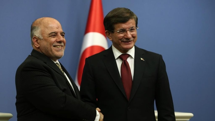 Turkish Prime Minister Ahmet Davutoglu, right, and his Iraqi counterpart Haider al-Abadi  shake hands after a news conference in Ankara, Turkey, Thursday, Dec. 25, 2014.(AP Photo)