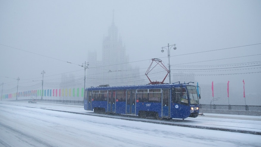 Dec. 25, 2014: A tram rolls through a snowstorm with a Stalin style building in the background, in Moscow