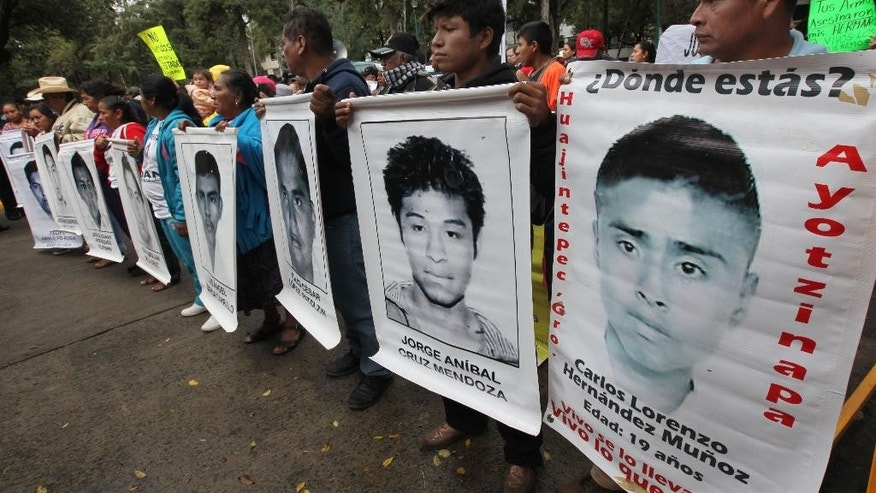 The relatives of 43 missing college students hold posters of their missing loved ones during a protest outside Germany's embassy in Mexico City, Thursday, Dec. 25, 2014. Demonstrators say German arms manufacturers exported rifles to a corrupt local police department implicated in the disappearance of 43 students. The police of Iguala, Mexico are accused of detaining the students on Sept. 26 and turning them over to a drug gang, which apparently killed them. (AP Photo/Marco Ugarte)