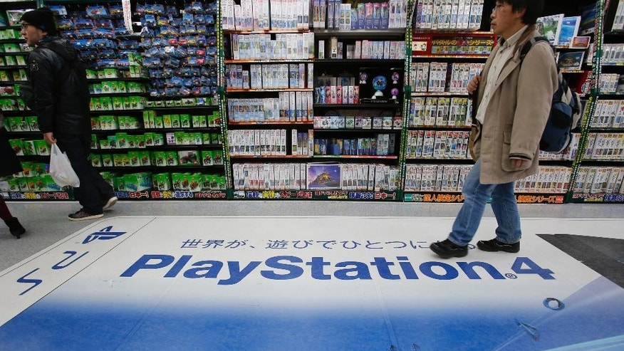 In this Thursday, Dec. 25, 2014 photo, a shopper walks on the logo of Sony's PlayStation 4 at an electronics store in Tokyo. Sony's online PlayStation store and Microsoft's Xbox site suffered disruptions to users on Christmas Day in the latest possible cyber-attacks on the companies. The PlayStation Store Twitter feed said Friday, Dec. 26 that some users were having trouble logging into its network. It said engineers were investigating. (AP Photo/Shizuo Kambayashi)