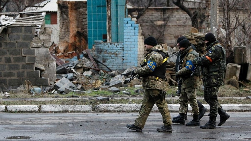 Ukrainian government army soldiers patrol an area in the village of Debaltseve, Donetsk region, eastern Ukraine Wednesday, Dec 24, 2014. Peace talks aimed at reaching a stable cease-fire in Ukraine between its government forces and pro-Russian armed groups began on Wednesday in Minsk, Belarus, with the discussions to include a pullout of heavy weapons and an exchange of war prisoners. (AP Photo/Sergei Chuzavkov)